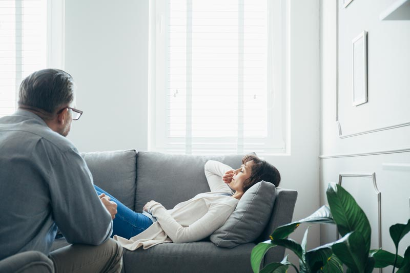 woman-at-therapy-room-laying-on-couch-discussing-w-UG75Z2Y.jpg